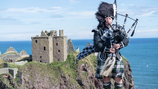 Piper with typical Scottish costume at Dunnottar Castle